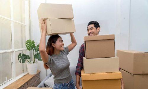 Pareja joven embalando cajas para poner en almacenamiento.