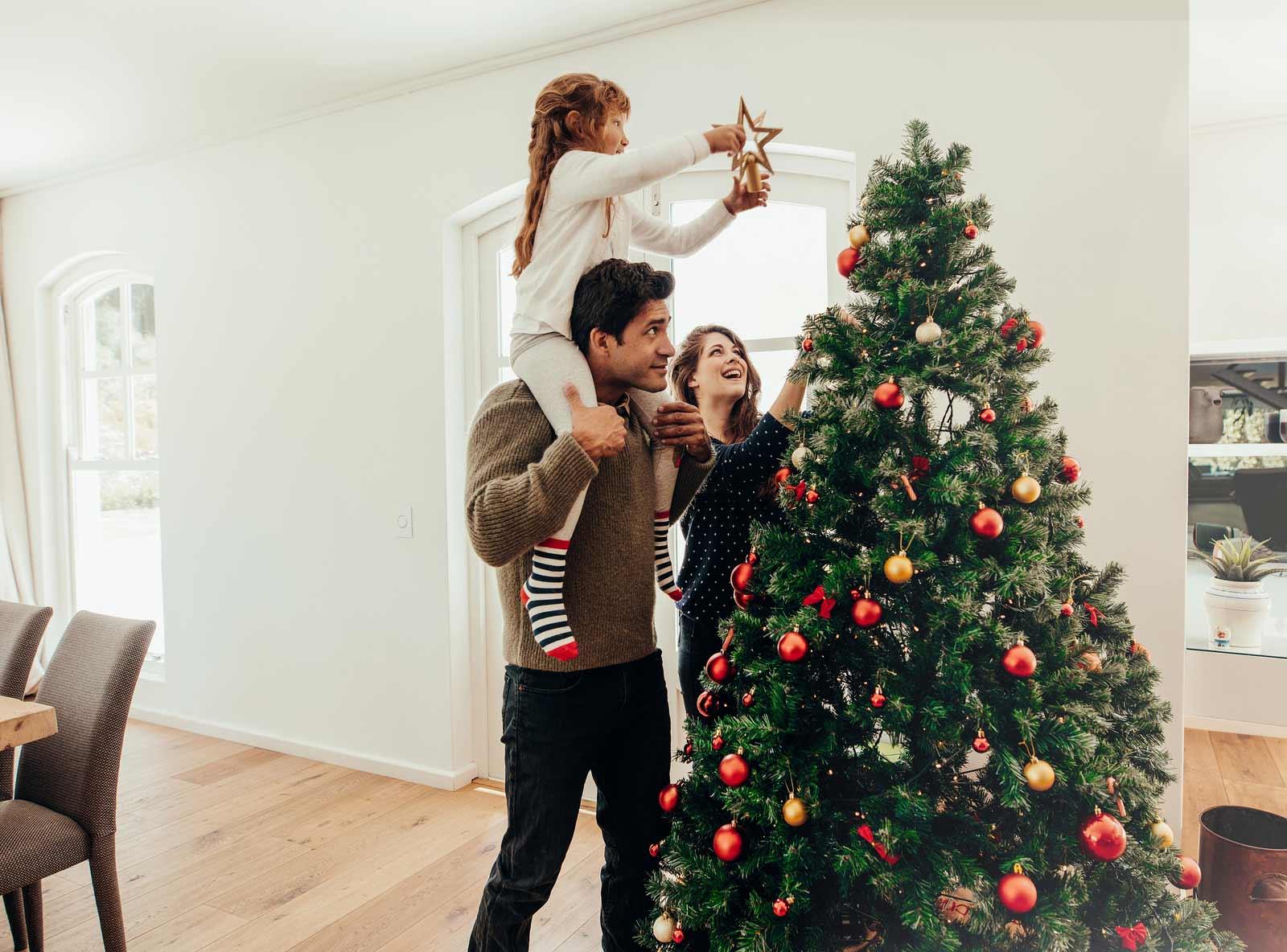 Une famille prépare son arbre de Noël pour les vacances des fêtes.