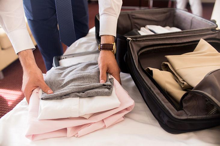 Un homme range ses vêtements dans une valise