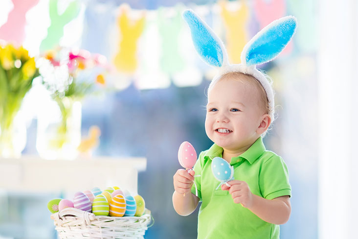 Niño pequeño sostiene decoraciones de Pascua de camino a la festividad.