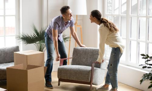 Couple moving chair to storage unit