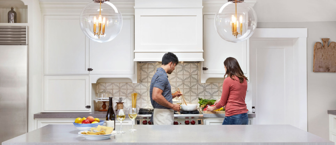 A couple prepares a meal in a white kitchen