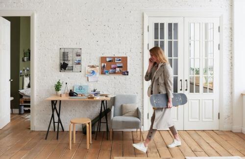 A woman walks through a spacious apartment holding a skateboard