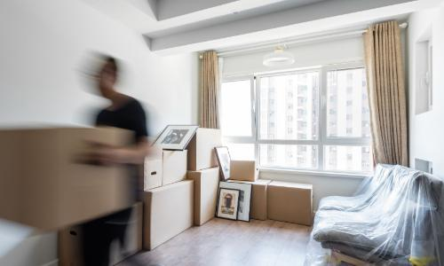 Man moving boxes from room
