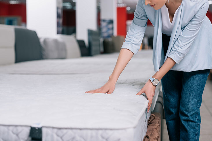 Woman prepares a mattress for self storage.
