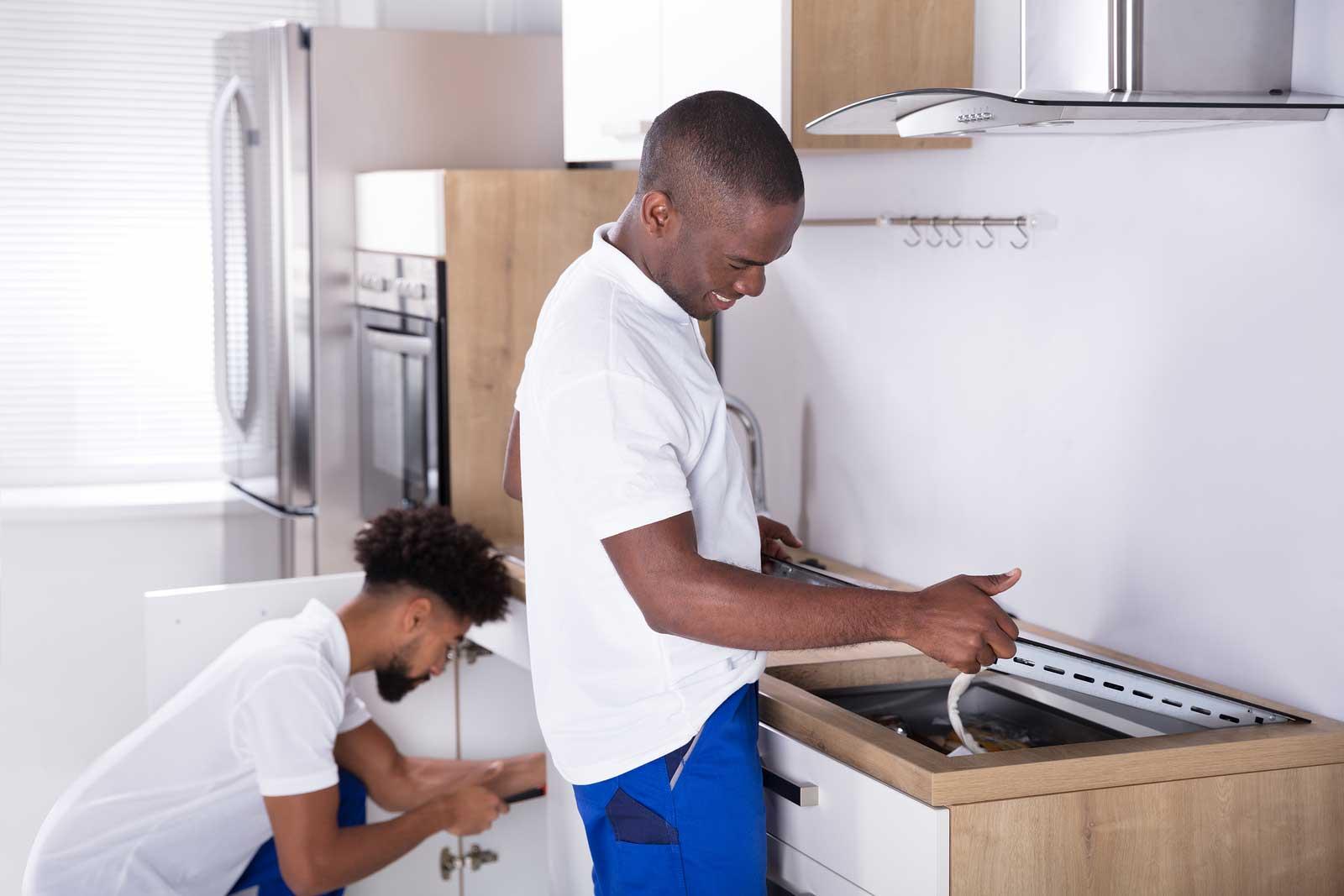 Deux hommes préparent une cuisinière pour l'entreposage
