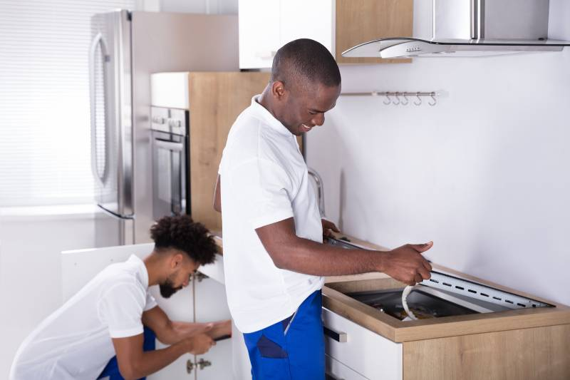 Deux hommes travaillent sur une cuisinière