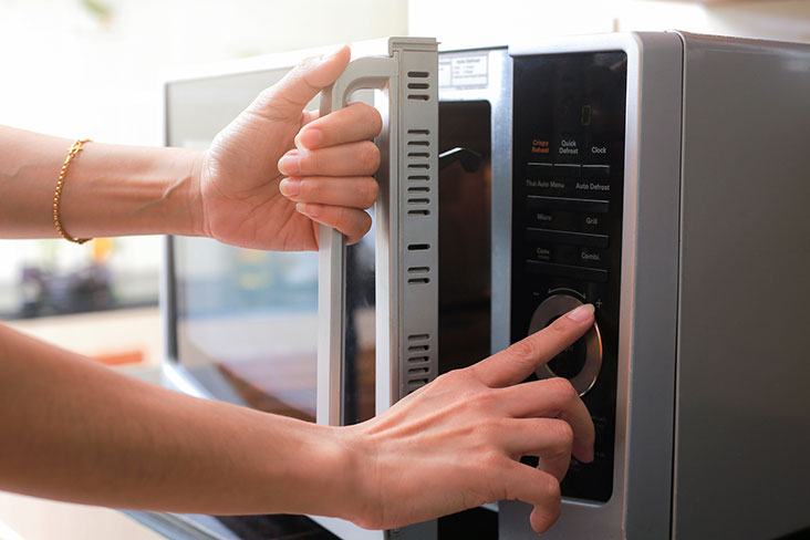 A woman prepares a microwave for a move to self storage