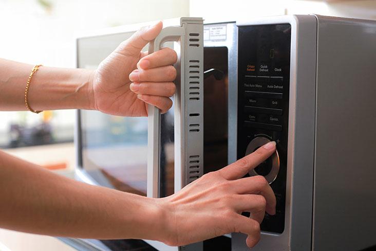Una mujer prepara un microondas para trasladarlo al almacenamiento.