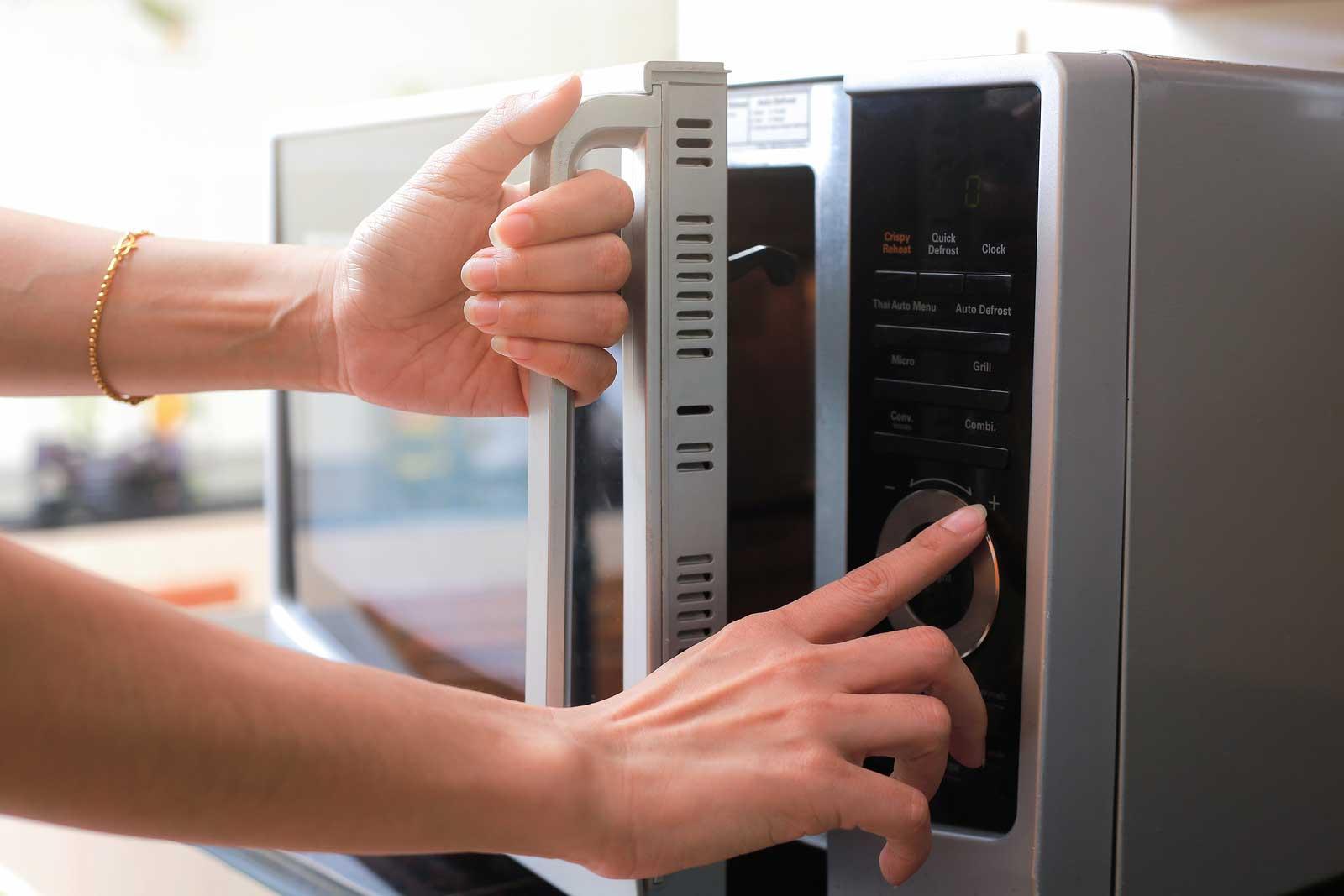 Une femme prépare un four à micro-ondes avant l'entreposage