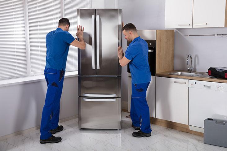 Deux hommes ont installé un réfrigérateur dans une cuisine