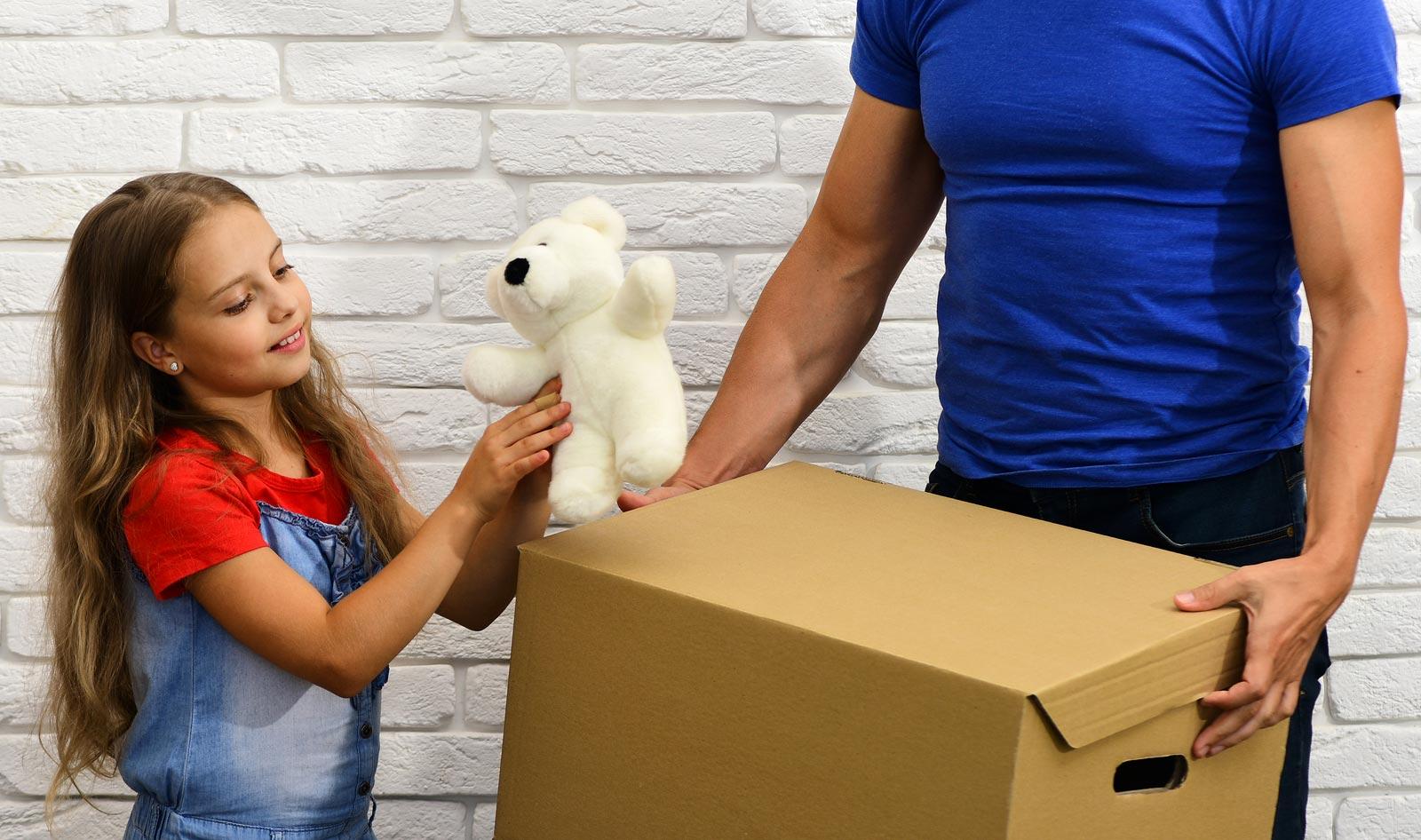 Une petite fille prépare un vieux jouet pour l'entreposage