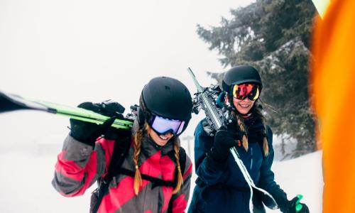 Girls carrying outdoor ski equipment