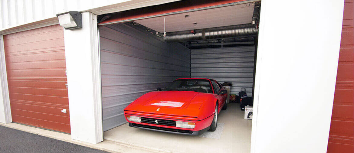 a red sports car parked in indoor parking storage