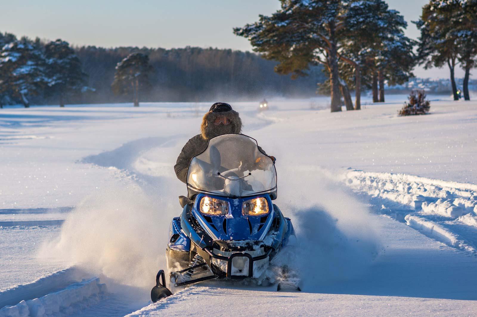 Une motoneige passe à travers un champ enneigé.