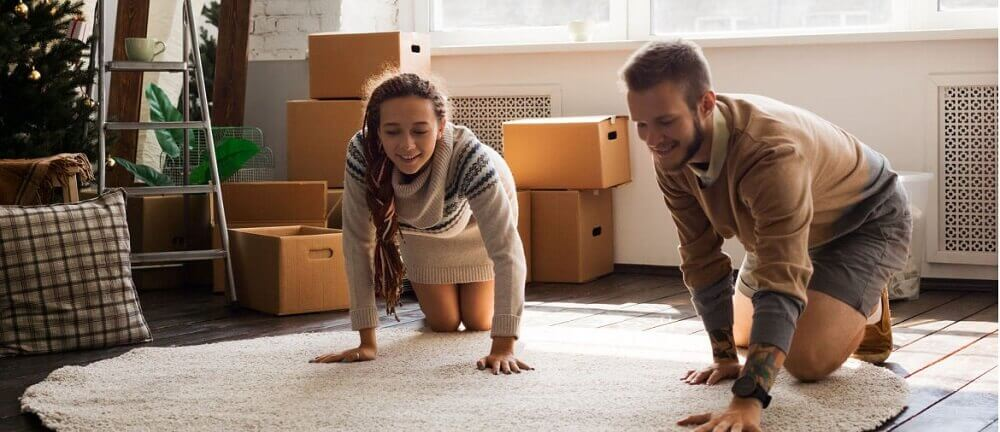 a young couple unpacks a rug in their new apartment
