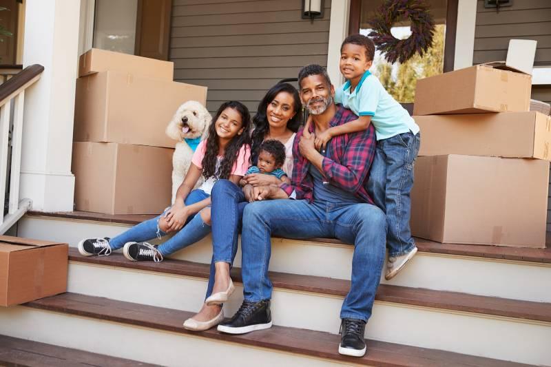 Une famille est assise sur le perron après avoir emballé les boîtes pour un déménagement ou un transfert.