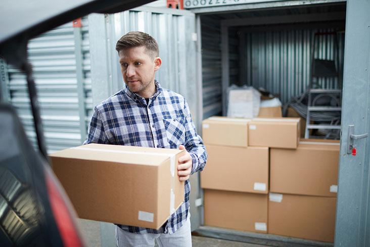 Young man packs a storage unit with belongings.