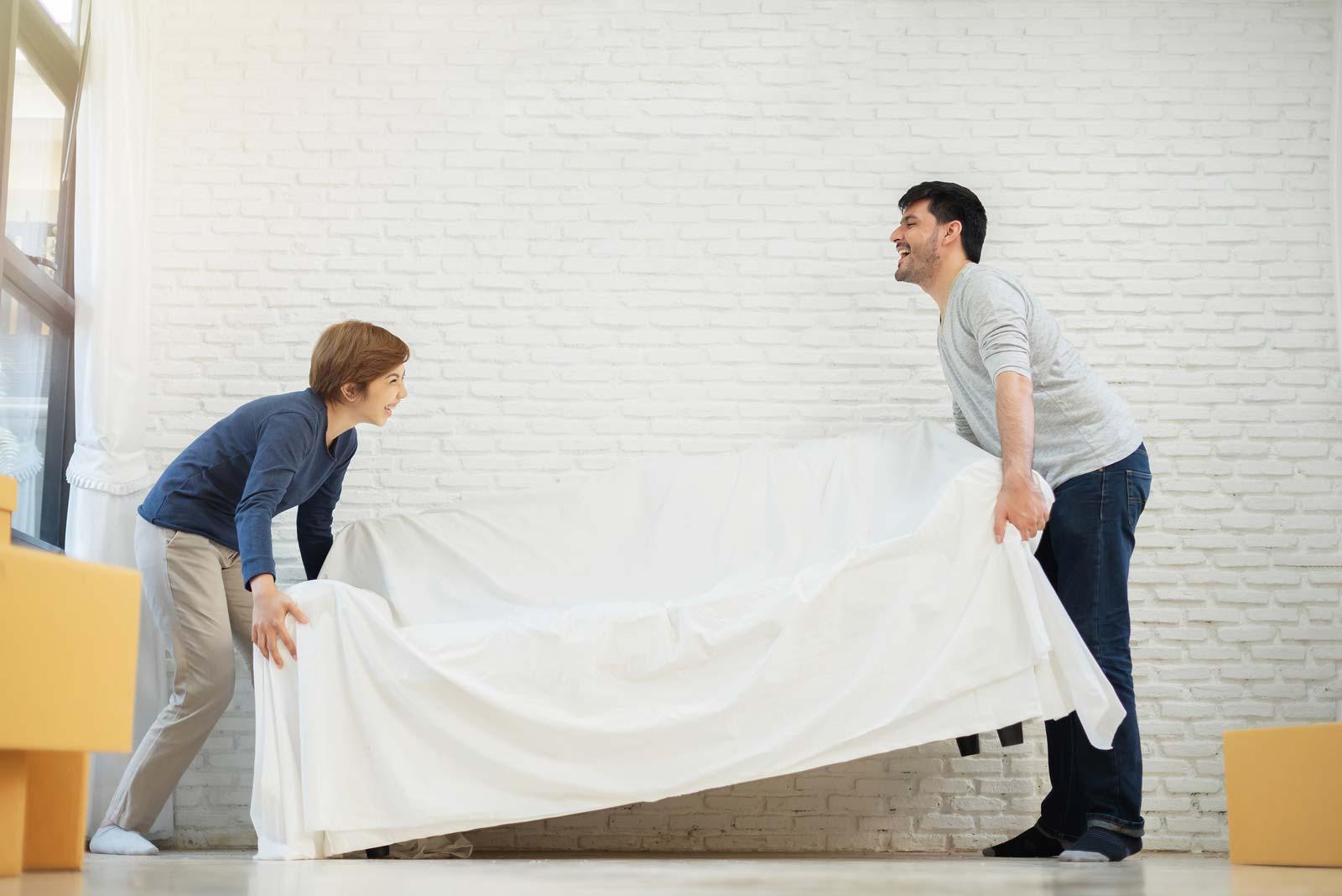 Un homme et un garçon transportent un sofa dans un local de stockage en libre-service