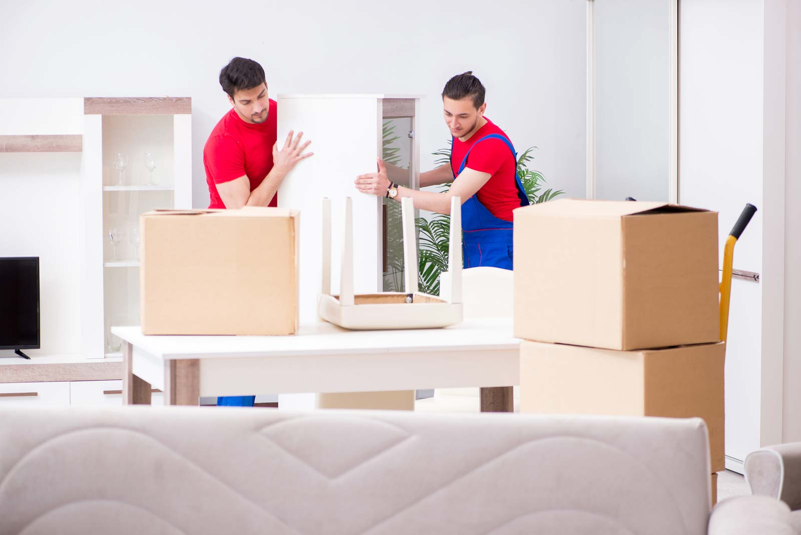 Movers remove boxes to prepare a table for storage.