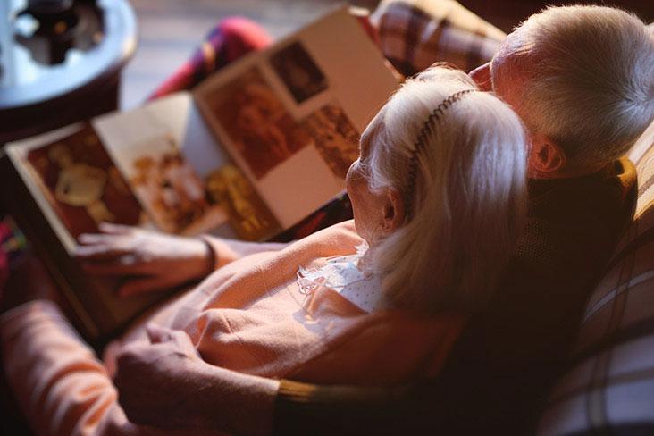 Hombre y mujer ven fotos familiares en un libro de recuerdos antes de almacenarlas.