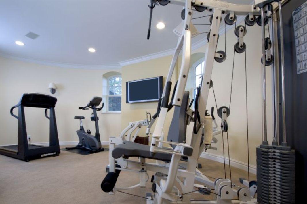 Un gymnase à domicile avec un tapis roulant, un vélo stationnaire, et d'autres équipements