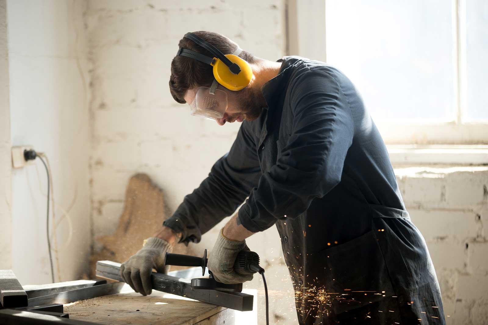 Hombre trabaja en proyecto de mejoras para el hogar con herramientas eléctricas.