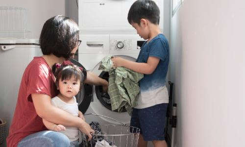 Family helping with laundry at the washing machine